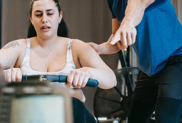 femme obèse faisant du rameur pour perdre du poids avec son coach sportif